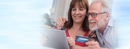 在网上购物与片剂和信用卡的成熟夫妇 免版税库存照片