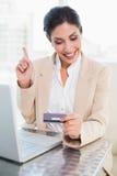 在网上购物与膝上型计算机和指向的愉快的女实业家 库存照片