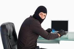 在网上购物与膝上型计算机的夜贼,当看照相机时 库存图片