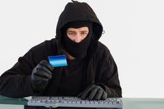在网上购物与膝上型计算机的夜贼,当看照相机时 免版税图库摄影