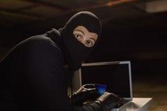在网上购物与膝上型计算机的夜贼,当看照相机时 免版税库存图片