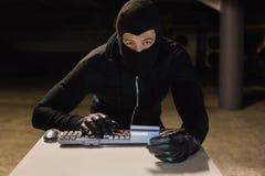 在网上购物与膝上型计算机的夜贼 免版税库存图片