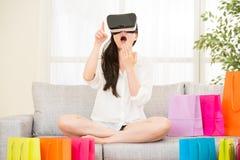 在网上购物与VR耳机的亚洲妇女感受惊奇 库存图片