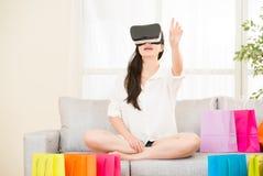 在网上购物与VR耳机的亚洲妇女经验 免版税库存照片
