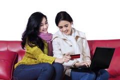 在网上购物两个俏丽的女孩 免版税库存照片