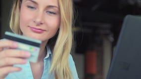 在网上购物使用她的信用卡和便携式计算机的美丽的妇女 股票视频