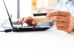 在网上购物使用有信用卡的膝上型计算机的人 库存照片