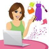 在网上购物使用有她的买一些时髦商品的信用卡的一台膝上型计算机的美丽的妇女 免版税库存图片