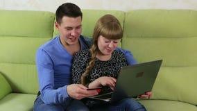 在网上购物和支付的滑稽的情感夫妇由信用塑料卡片 影视素材