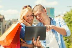 在网上购物愉快的年轻的夫妇 库存照片