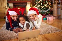 在网上购物的圣诞节的美国黑人的家庭用途膝上型计算机 库存照片