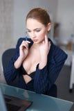 在网上玻璃的性感的白肤金发的妇女在办公室挥动 库存图片