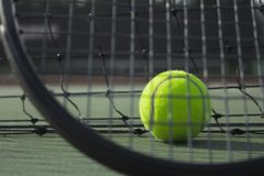 在网球场和球拍的网球 免版税库存照片