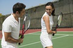 在网球场的女子和男性网球辅导员实践的球拍控制 免版税库存图片