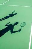 在网球场的球员阴影 免版税库存照片