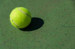 在网球场的绿色,黄色网球 免版税库存图片