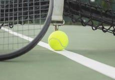 在网球场线和球拍的网球 免版税图库摄影
