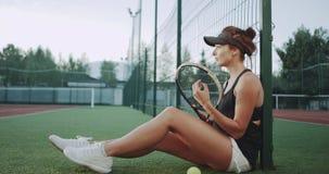 在网球场sportiv妇女为网球比赛做准备,坐地板和放松 股票视频