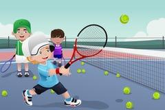 在网球实践的孩子 免版税库存图片