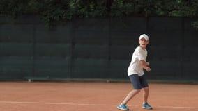 在网球的戏剧,坚定的集中和集中于比赛和球拍的运动员青少年的男孩打在红色法院的球 股票录像