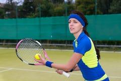 在网球草cou的美丽的年轻女性网球员服务 免版税库存照片