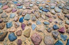 在罕见的石头的古老铺路石在沙子 免版税库存照片