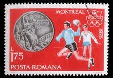 在罗马尼亚、展示手球和奥林匹克圆环打印的邮票 免版税图库摄影