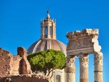 在罗马广场的专栏的特写镜头有教会圆屋顶的在罗马,它 库存图片