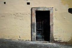 在罗马意大利染黑被烧的门,对比与它` s苍白桃子墙壁和年迈的框架, 免版税库存照片