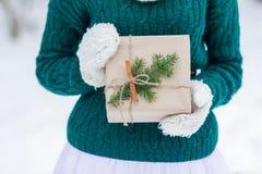 在羊毛制手套的欢乐包裹的牛皮纸圣诞节礼物 免版税库存照片