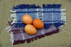 在羊毛织品的三个棕色鸡鸡蛋 库存照片
