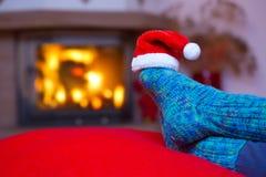 在羊毛蓝色袜子和圣诞老人帽子的脚 免版税库存图片