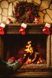 在羊毛袜子的脚由壁炉 妇女由温暖的fi放松 库存图片