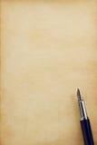 在羊皮纸的墨水笔 库存照片