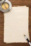 在羊皮纸背景的墨水笔和指南针 免版税库存图片