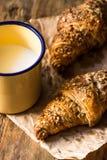 在羊皮纸,搪瓷杯子的全麦新月形面包用在木厨房用桌上的牛奶在早晨光 图库摄影
