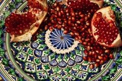 在美丽的传统中东黏土板材的成熟和新鲜的石榴种子 免版税库存图片