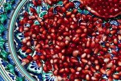 在美丽的传统中东黏土板材的成熟和新鲜的石榴种子 免版税图库摄影