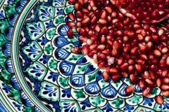 在美丽的传统中东黏土板材的成熟和新鲜的石榴种子 免版税库存照片