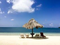 在美丽的加勒比海滩的Tiki小屋在离洪都拉斯的海岸的附近 免版税库存照片