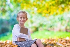 读在美丽的可爱的小女孩一本书 免版税库存照片