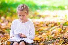 读在美丽的可爱的小女孩一本书 免版税库存图片