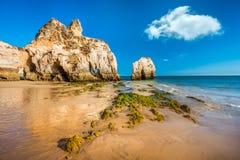 在美丽的多岩石的海滩-普腊亚Dos Tres Irmaos,阿尔加的低潮 免版税库存图片