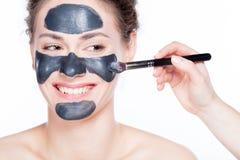 在美丽的妇女的黑木炭面具应用 库存图片