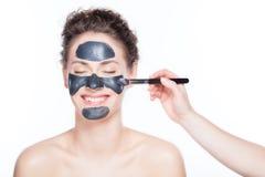 在美丽的妇女的黑木炭面具应用 免版税库存照片