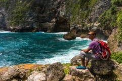 在美丽的小海湾坐岩石和观察海的年轻人 图库摄影
