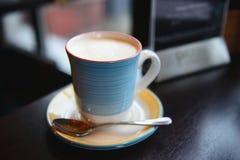 在美丽的杯子的鲜美热奶咖啡 免版税图库摄影