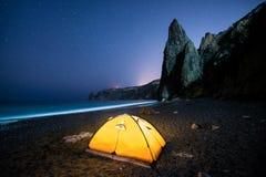 在美丽的海岸的发光的野营的帐篷与岩石在晚上在满天星斗的天空下 库存照片