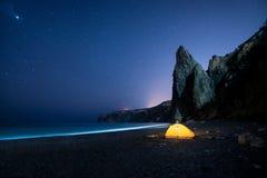 在美丽的海岸的发光的野营的帐篷与岩石在晚上在满天星斗的天空下 库存图片
