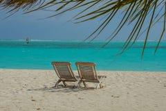 在美丽的海滩的两把椅子在手段的热带海岛 免版税库存照片